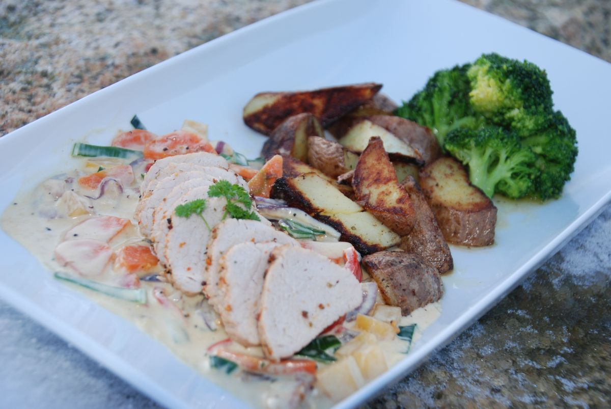 Pork fillet with vegetables, fried potatoes and creamy sauce